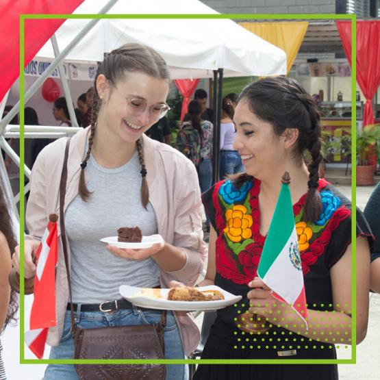 Imagen para la sección internacionalización en casa de dos mujeres compartiendo recetas de sus países de origen en la Feria gastronómica en Unibagué